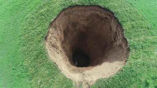 Когда проваливается земля, образуются так называемые карстовые провалы, либо осыпаются давно заброшенные ямы. Как они выглядят? Изредка близки к цилиндру, но преимущественно расширяются к верху.
